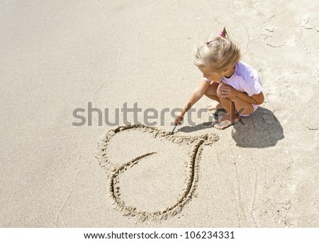 Pretty small girl drawing a heart shape on sand - stock photo