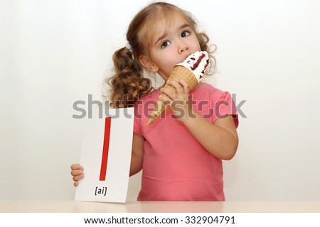 Pretty small girl eating an ice-cream on the white background with I letter on it, indoor portrait - stock photo