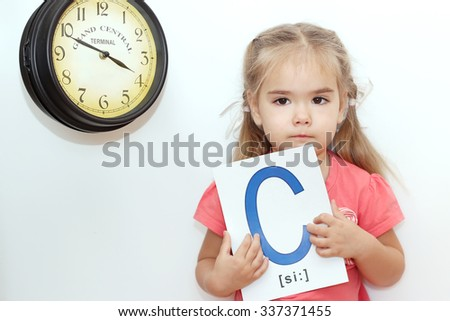 Pretty small girl holding a picture with C letter on it over white background with old clock, indoor portrait, ABC concept - stock photo