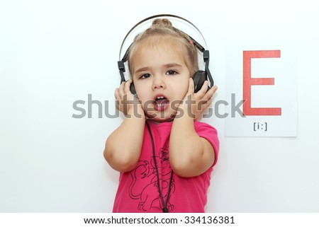 Pretty small girl in the earphones listening to music and signing over white background with E letter on it, indoor portrait - stock photo