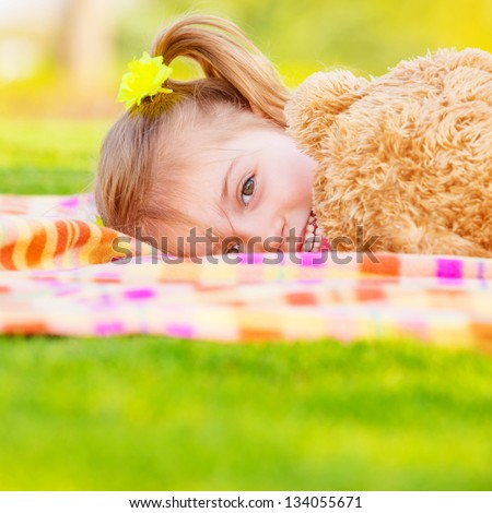 Pretty small girl lying down on green field, playing game with big brown teddy bear, cute child enjoying spring nature - stock photo