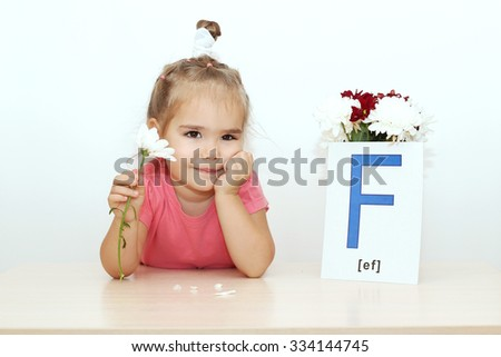 Pretty small girl telling fortunes with flower near the bouquet and picture with F letter over white background, indoor portrait - stock photo
