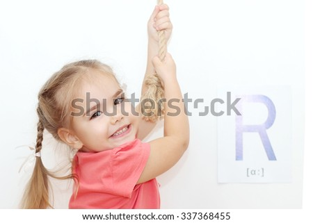 Pretty small girl with plaits pulling a rope and looking up over white background with R letter on it, indoor portrait, ABC concept - stock photo