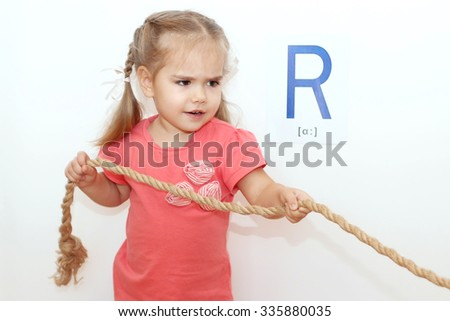 Pretty small girl with plaits pulling a rope over white background with R letter on it, indoor portrait - stock photo