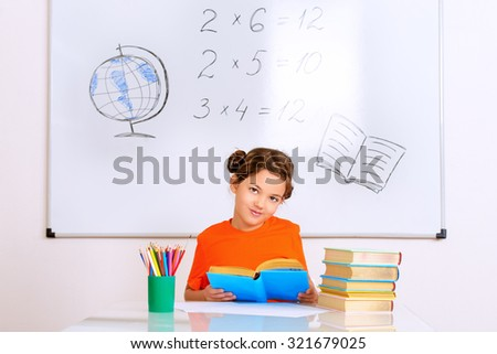Pretty smart schoolgirl sitting at the desk in the classroom on blackboard background. Education. - stock photo