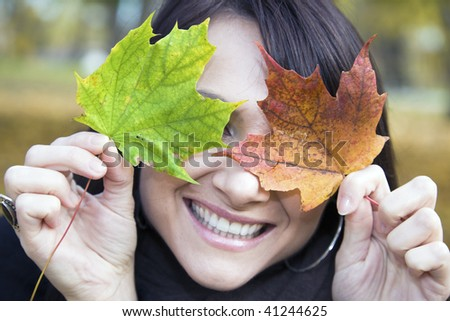Pretty smile and colorful leaves - middle of the fall. - stock photo