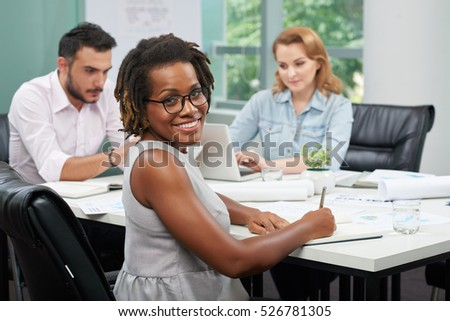 Pretty smiling African-American business lady working in office