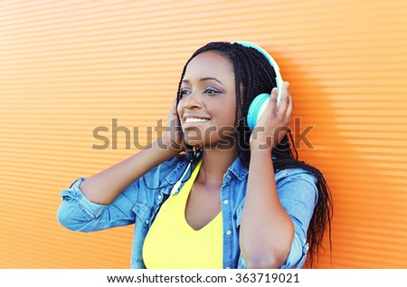 Pretty smiling african woman with headphones enjoying listens to music over orange background - stock photo