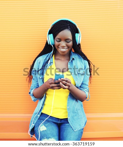Pretty smiling african woman with headphones listens to music over orange background - stock photo