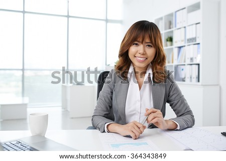 Pretty smiling Asian business lady sitting at desk in her office - stock photo