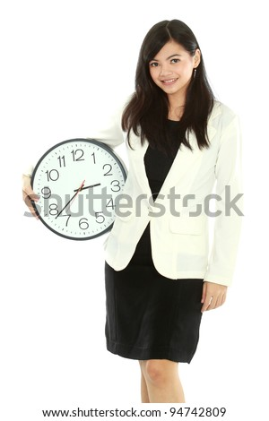Pretty smiling asian business woman holding a clock - stock photo