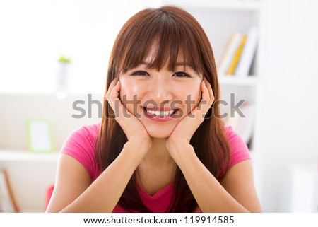 Pretty smiling Asian girl holding her face sitting at home - stock photo