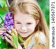 Pretty smiling blond little girl with flowers of blooming lilac in her hands  - stock photo