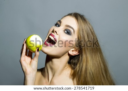 Pretty smiling blonde girl with bright make up looking forward holding fresh green apple standing on gray background copyspace, horizontal picture - stock photo
