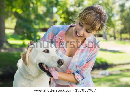 Pretty smiling blonde posing with her labrador in the park on a sunny day - stock photo