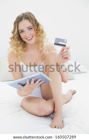 Pretty smiling blonde sitting on bed holding tablet and credit card in bright bedroom