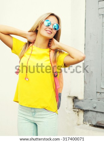 Pretty smiling blonde woman wearing a sunglasses and yellow t-shirt in the city, street fashion - stock photo