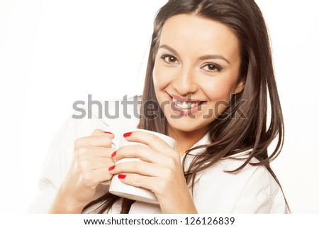 pretty smiling brunette in a white men's shirt holding cup of tea on white background - stock photo