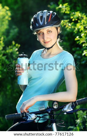 Pretty smiling cyclist girl with a  bottle of water - stock photo
