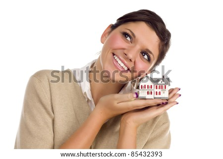 Pretty Smiling Ethnic Female Daydreaming with Small House Isolated on a White Background. - stock photo