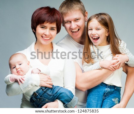 Pretty smiling family looking at the camera - stock photo