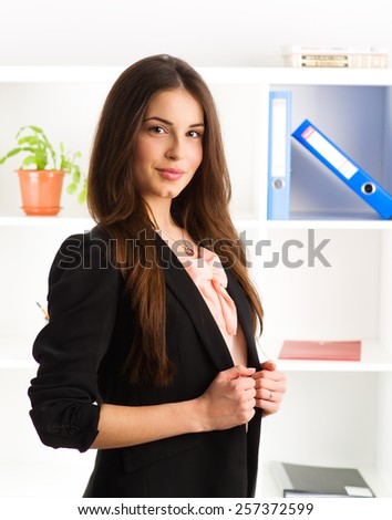 Pretty smiling female legal expert wearing suit standing in the office. Concept of partnership and success.  - stock photo