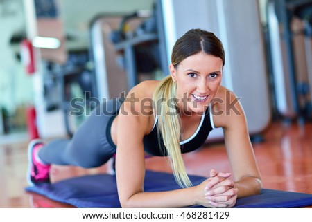 Pretty smiling fitness trainer doing push-ups in the gym. Young sportswoman exercising at aerobics class. Healthcare and weight loss concept.