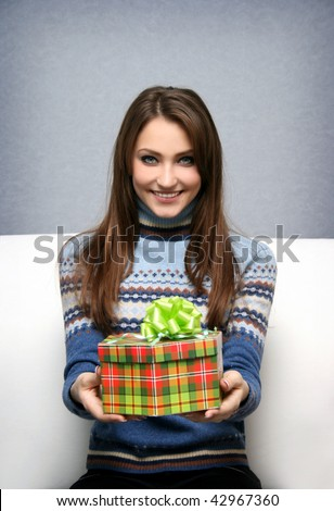 Pretty smiling girl gives a gift in packing