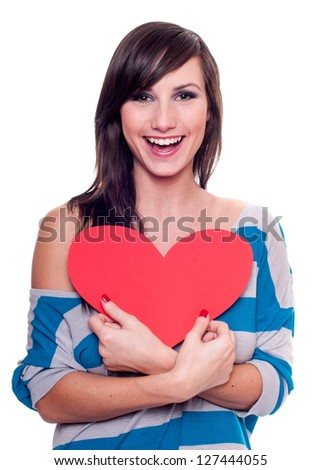Pretty smiling girl holding a red heat isolated on white - stock photo