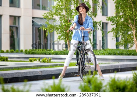 Pretty smiling girl in hat and blue dress riding a bicycle at green street of town - stock photo
