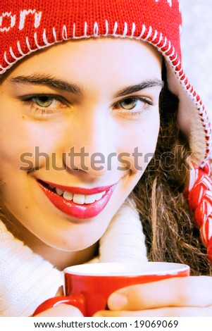Pretty smiling girl  in winter clothes with a red cup of hot drink. Could be coffee, cappuccino, chocolate, tea. Warm and winter concept. - stock photo