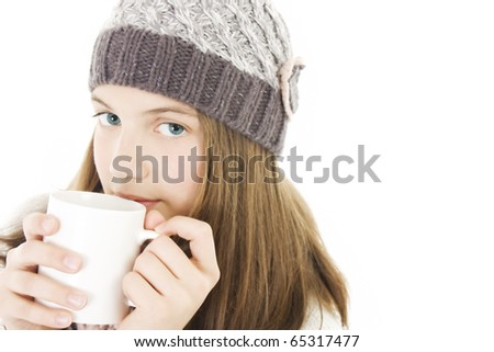 Pretty smiling girl in winter clothes with a  white cup of hot drink.