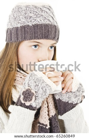 Pretty smiling girl in winter clothes with a  white cup of hot drink. Could be coffee, cappuccino, chocolate, tea.