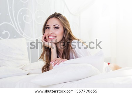 Pretty smiling girl is lying in bed with white pillows - stock photo