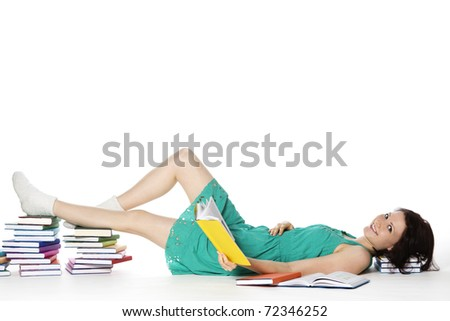 Pretty smiling girl lying on floor resting feet and head on colorful book stacks reading, isolated on white background with plenty of copy-space. - stock photo