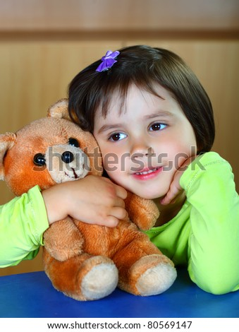 Pretty smiling girl playing with teddy bear soft toy
