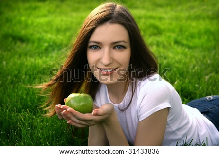 Pretty smiling girl relaxing outdoor with apple - stock photo