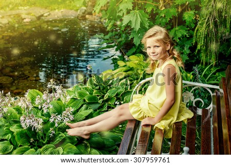 Pretty smiling girl resting in summer park. Happy childhood. Holidays.  - stock photo