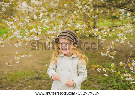 Pretty smiling girl standing near blossom apple tree