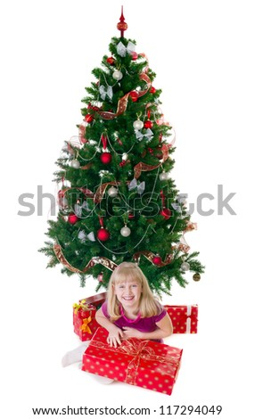 Pretty smiling girl with a gift under the Christmas tree isolated on white - stock photo
