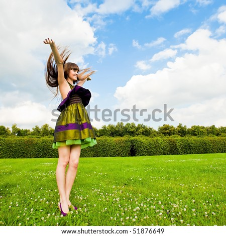 Pretty smiling girl with long brown hairs on green meadow - stock photo