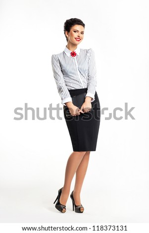 Pretty smiling happy secretary with notebook standing in studio - stock photo