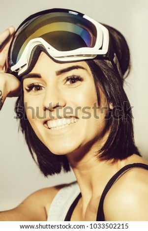 pretty smiling happy woman or sexy girl with cute face in safety glasses or ski goggles for winter sport on grey background