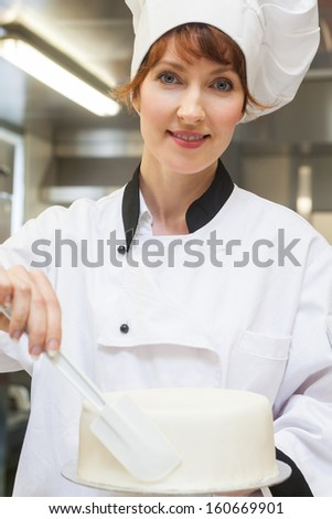 Pretty smiling head chef finishing a cake with icing in professional kitchen - stock photo