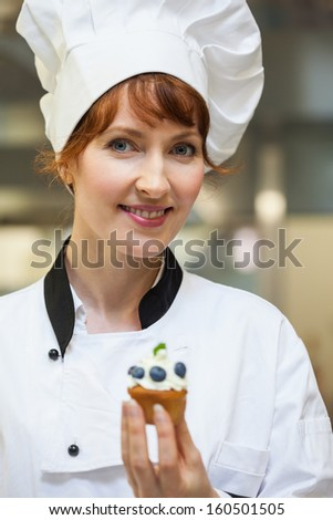 Pretty smiling head chef holding blueberry dessert in professional kitchen - stock photo