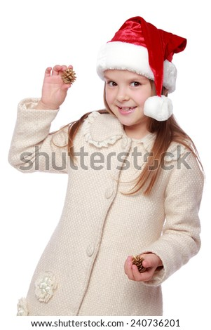 Pretty smiling little girl in Santa's red hat holding a Christmas pine cone/Image of happy young girl in a Santa hat enjoys and laughing on white background