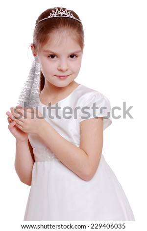 Pretty smiling little girl is holding a small Christmas tree isolated on white