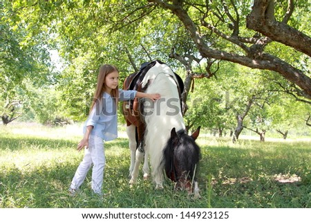 Pretty smiling little girl walking with a charming pony in the apple garden/Pony in the meadow eating green grass - stock photo