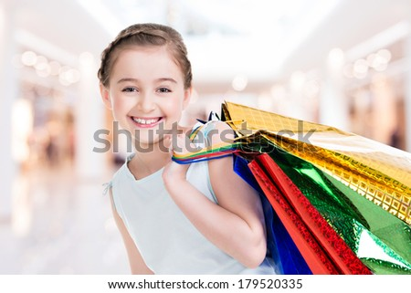 Pretty smiling little girl with shopping bags posing  in the shop