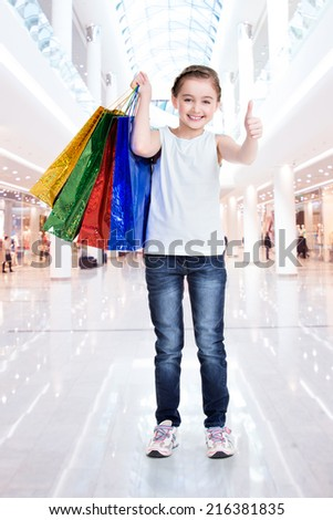 Pretty smiling little girl with shopping bags with thumb up sign in the shop - stock photo